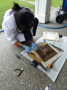 Conservator removes wet mats from a print